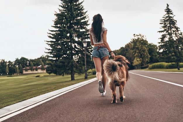 Wie komt eerst? achteraanzicht van de volledige lengte van een jonge vrouw die met haar hond door het park rent terwijl ze tijd buitenshuis doorbrengt
