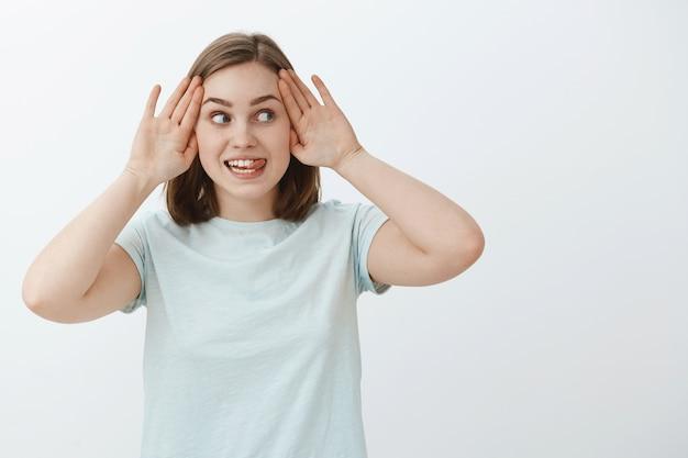Wie verstopt zich niet rennen. portret van geamuseerde en grappige charmante jonge speelse vrouw in lichtblauw t-shirt tong uitsteekt van opwinding kiekeboe spelen en naar rechts staren met opgewonden uitdrukking