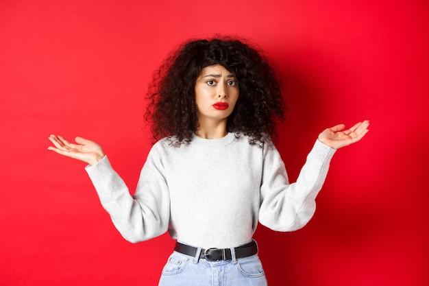 Wie weet. clueless jonge vrouw met krullend haar, schouderophalend en verward kijkend, staande in vrijetijdskleding op rode achtergrond