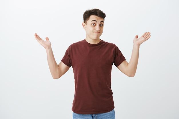 Wie wist dat het zou gebeuren. portret van clueless onbewust aantrekkelijke man in rood t-shirt