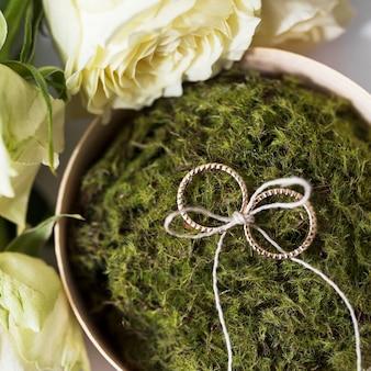 Wiedende ringen die met koorden op mos worden gebonden dat met rozen wordt gezet