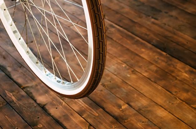 Wiel van een stijlvolle fiets met een witte velg en een bruine rubberen band op een stijlvolle houten