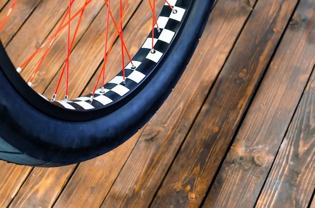 Wiel van een stijlvolle fiets met een zwart-witte velg en een zwarte rubberen band op een stijlvolle houten achtergrond.