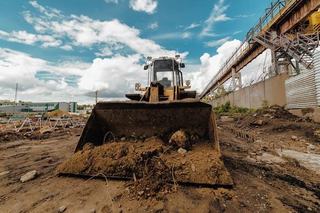 Wiellader met een volle emmer grond. productie van grondwerken.