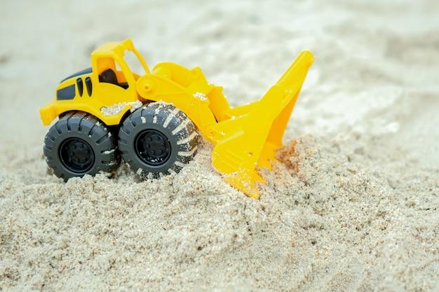 Wiellader speelgoed op zand, constructeur speelgoedvoertuig