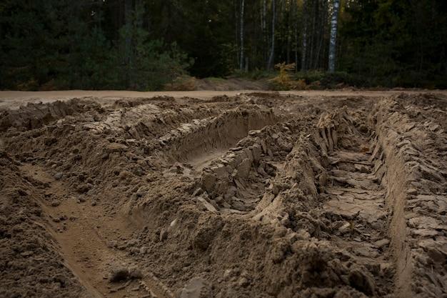 Wielspoor op zandgrond van groot transport, tractor op bouwplaats, zandweg. hoge kwaliteit foto