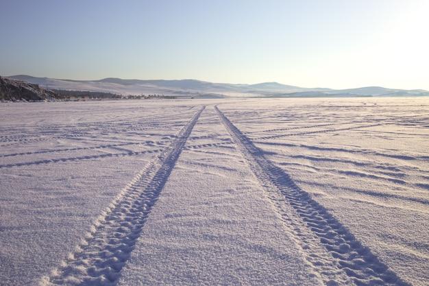 Wielsporen op de de winterweg met sneeuw wordt behandeld die