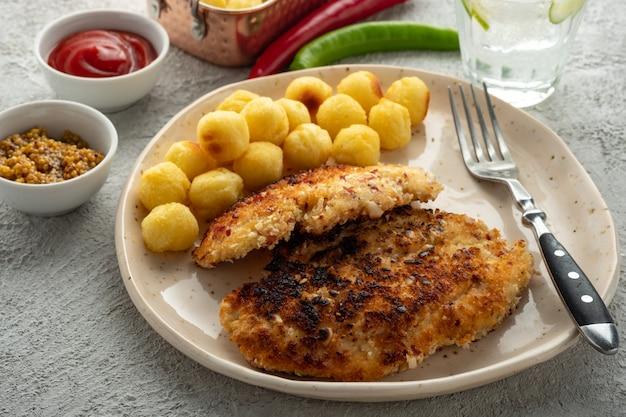 Wiener schnitzel met aardappelballetjes en citroensaus. kipschnitzel in paneren