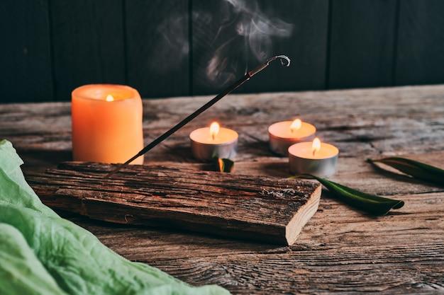 Wierookstok en kaarsen op rustiek hout