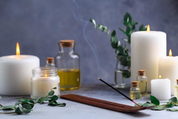 Wierookstokje met rook op steen met witte kaarsen en etherische oliën
