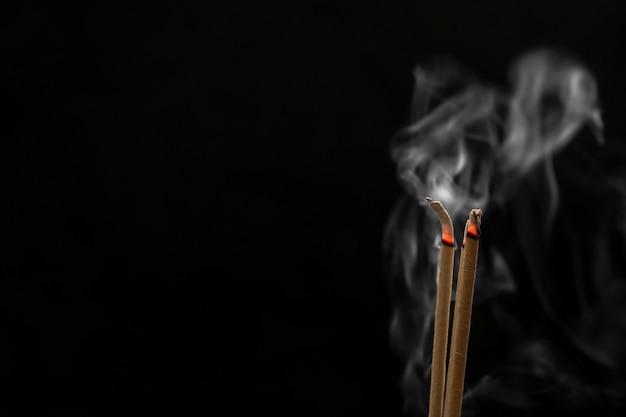Wierookstokjes en wierookstokjesrook op zwarte achtergrond