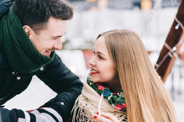Wij houden van de winter. taille portret van blij jong liefdevol paar kijken elkaar aan en glimlachen. ze dragen warme jassen en sjaals