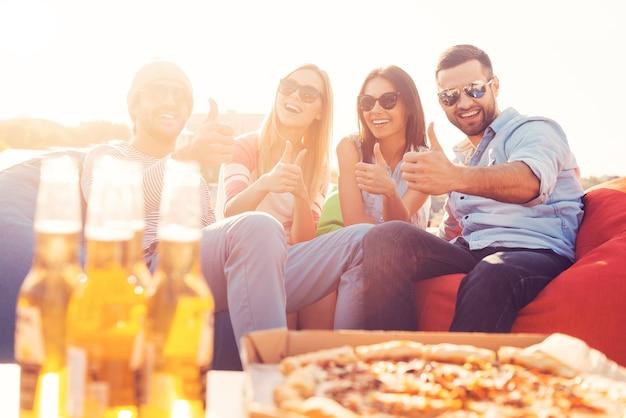 Wij houden van pizza en bier! vier jonge vrolijke mensen die hun duimen opsteken en glimlachen terwijl ze op zitzakken zitten met pizza en bier op de voorgrond