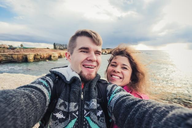 Wij houden van reizen. avontuurlijke selfie. kaukasisch jong stel dat selfie neemt terwijl ze op de bergen in de buurt van de zee wandelen.