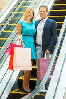Wij houden van samen winkelen! volledige lengte van een vrolijk volwassen stel dat boodschappentassen vasthoudt en glimlacht terwijl ze zich met de roltrap verplaatsen