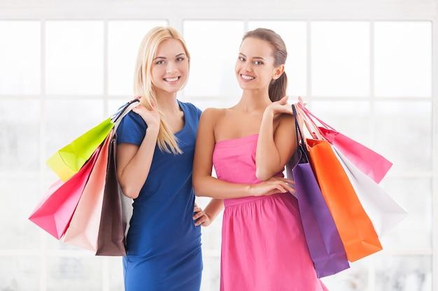 Wij houden van winkelen. twee aantrekkelijke jonge vrouwen in jurken die dicht bij elkaar staan en boodschappentassen vasthouden