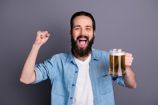 Wij kampioenen! extatisch funky gekke kerel voetbal sportfan minnaar kijken wereldbeker genieten van vrije tijd houden glas bier vuisten heffen schreeuwen ja dragen denim jeans overhemd geïsoleerd grijze kleur muur