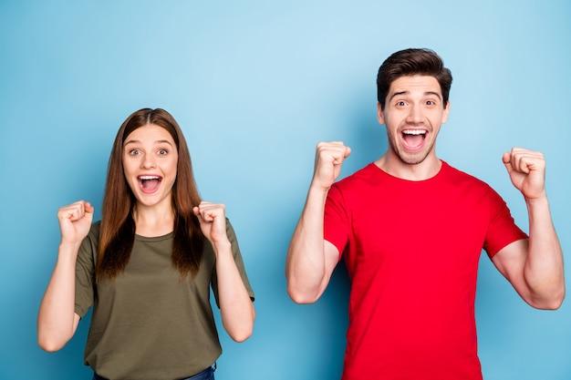 Wij kampioenen omg! portret van positieve vrolijke echtpaar horen prachtige loterij winnende nieuws vuisten verhogen schreeuwen wow dragen groen rood t-shirt geïsoleerd op blauwe kleur achtergrond