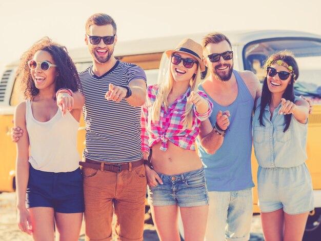 Wij kiezen jou! groep vrolijke jonge mensen die je wijzen en glimlachen terwijl ze op het strand staan met een retro minibusje op de achtergrond