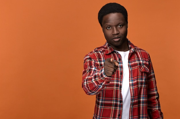 Wij kiezen jou. stijlvolle aantrekkelijke jonge afro-amerikaanse man in geruite overhemd met ernstige zelfverzekerde gezichtsuitdrukking, wijzende wijsvinger poseren tegen lege oranje muur