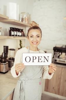 Wij zijn geopend. mooie lachende startup-eigenaar die gasten van haar nieuwe café begroet.