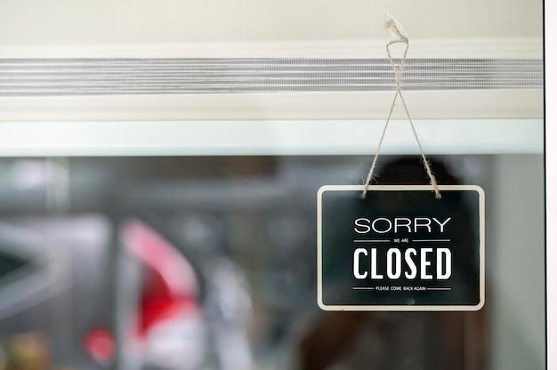 Wij zijn gesloten uithangbord kijkend door het glas van de etalage.