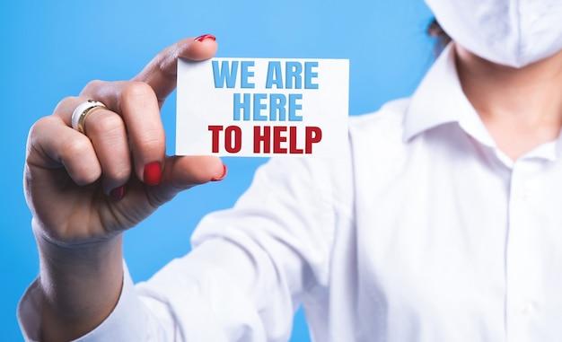 Wij zijn hier om te helpen geschreven op een wit blad dat door een arts wordt vastgehouden. sponsoring concept. medisch concept.