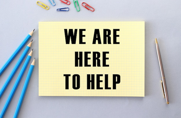Wij zijn hier om te helpen tekst in notitieboekje op grijs naast potloden, pen en paperclips. concept.