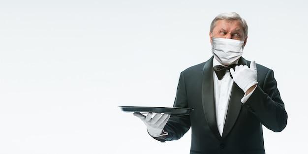 Wij zijn open. elegantie senior man ober in beschermend gezichtsmasker op witte achtergrond. flyer met copyspace. café, restaurantopening. veiligheid tijdens een pandemie van het coronavirus. verzorgen van gasten, klanten.