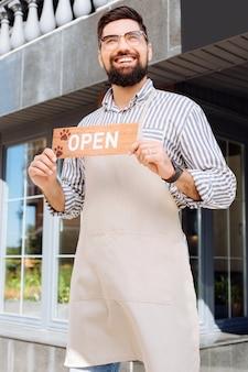 Wij zijn open. opgetogen blije man met een openingsbord terwijl hij voor het café staat