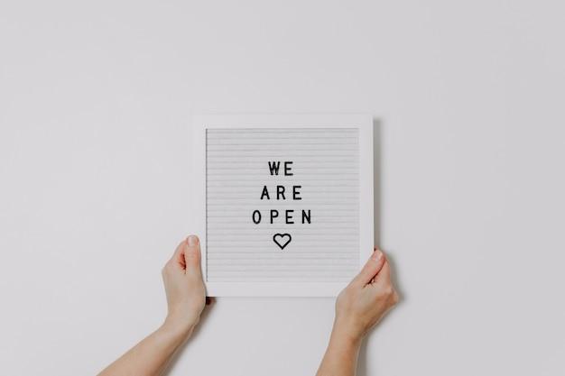 Wij zijn open teken voor kleine bedrijven. handen met een wit letterbord met woorden. winkel heropend, einde lockdown.