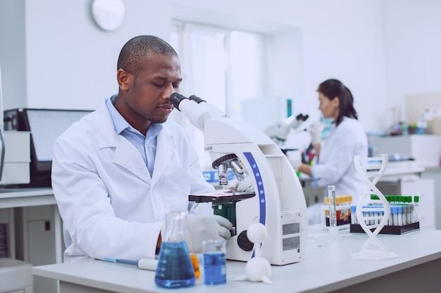 Wij zijn professionals. geïnspireerde professionele bioloog die met zijn microscoop werkt en zijn collega die op de achtergrond werkt