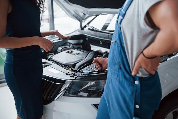 Wij zorgen hiervoor. vrouw in de autosalon met werknemer in blauw uniform die haar gerepareerde auto terugneemt