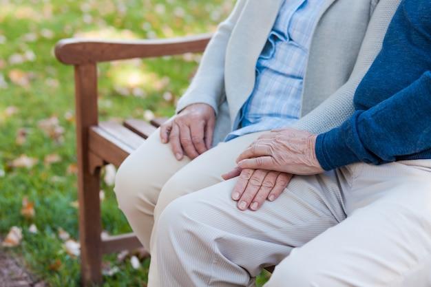 Wij zullen altijd samen zijn. close-up van senior koppel hand in hand terwijl ze samen op de bank in het park zitten