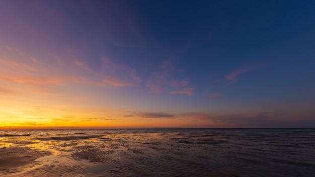 Wijd geschoten van natte strandkust onder een blauwe en gele hemel bij zonsondergang