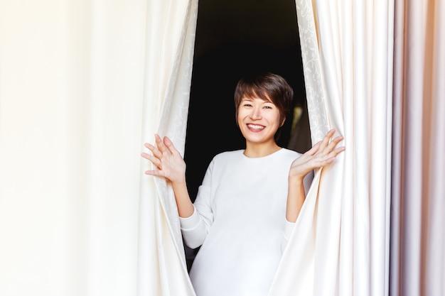 Wijd glimlachende mooie aziatische vrouw opent gordijnen op venster.