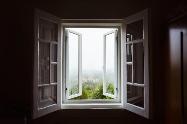 Wijd open raam met een prachtig uitzicht op het platteland op mistige dag. blijf thuis concept. uitzicht op het landschap vanuit het huis. reis naar spanje en vakantieconcept. open een raam om de kamer te luchten. ventileer uw huis.