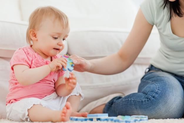 Wijfje dat een raadselstuk toont aan haar baby terwijl het zitten op een tapijt