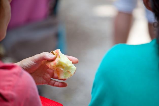 Wijfje dat een rode gebeten appel houdt