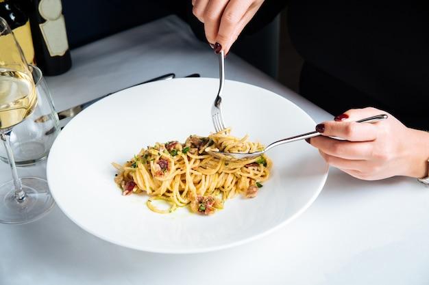 Wijfje dat italiaanse spaghetticarbonara met witte wijn eet
