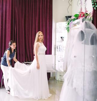 Wijfje dat op huwelijkskleding probeert in een winkel met vrouwenmedewerker.