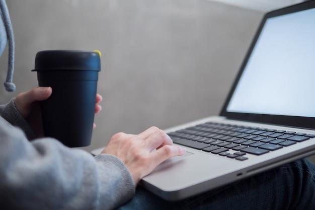 Wijfje dat op laptop gebruikt en mokkoffie houdt.