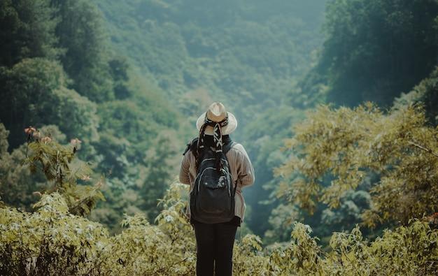 Wijfje dat zich op een heuvel bevindt die over de wildernis kijkt