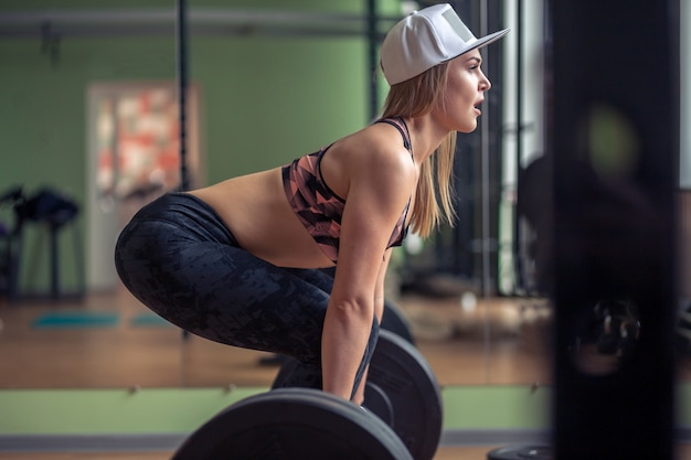 Wijfje die deadlift oefening met gewichtsbar uitvoeren. zekere jonge vrouw die gewichtheffentraining doen bij gymnastiek