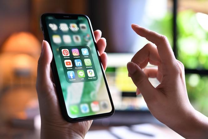 Wijfje die een smartphone met pictogrammen van sociale media thuis op het scherm houden