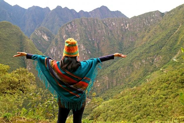 Wijfje die haar wapens opheft bij het gezichtspunt op de berg van huayna picchu, machu picchu, cusco region, peru
