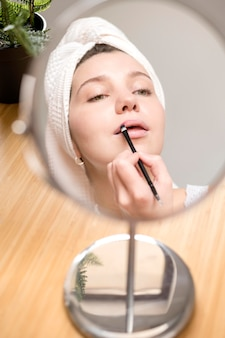 Wijfje die lippenstift in spiegel toepassen