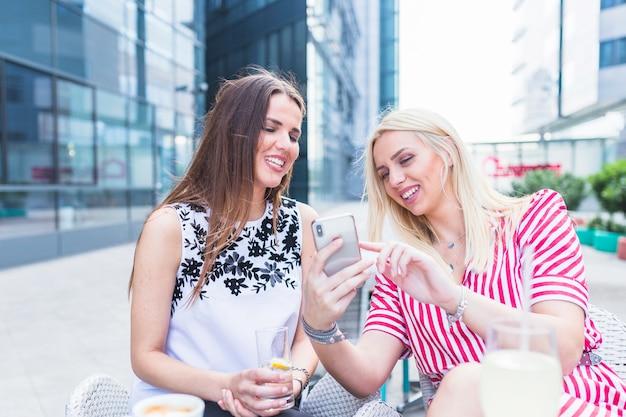 Wijfje die mobiele telefoon tonen aan haar vriendenzitting bij openluchtkoffie