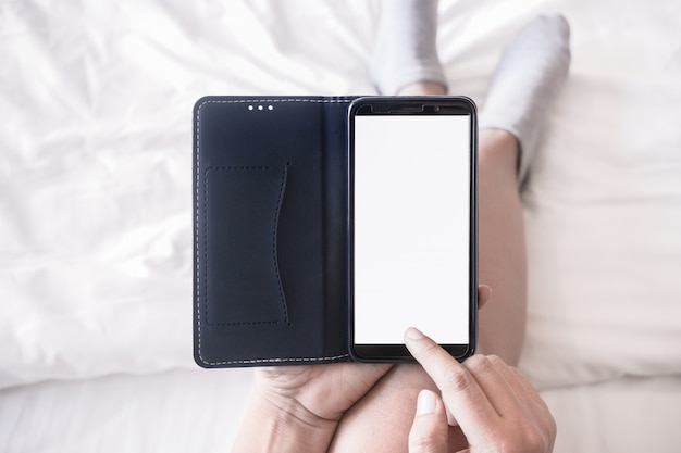 Wijfje die op wit bed liggen die slimme telefoon in hoogste meningspositie met behulp van, het lege smartphone mobiele scherm voor model of presentatie.