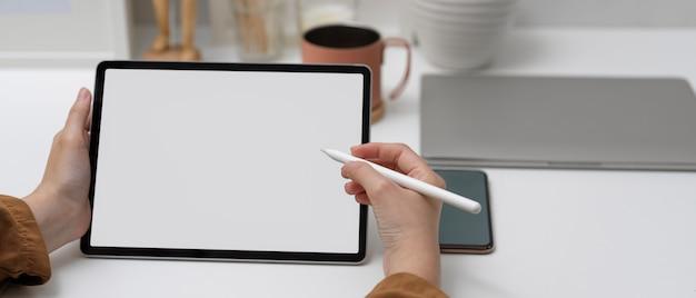 Wijfje die spot op tablet met naaldpen gebruiken op witte lijst in huisbureau